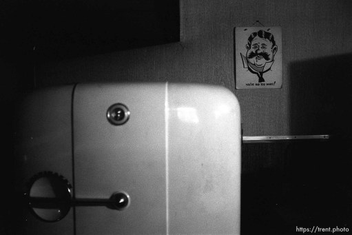 """Fridge and picture of four-eyed man reading """"you've had too many!"""" at Nana's house."""