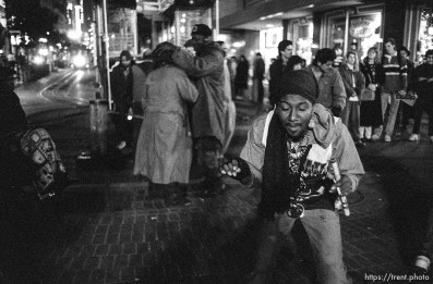 Man dancing on Market Street at night.