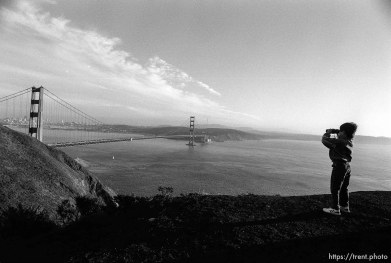 Kid with binoculars and view of Golden Gate Bridge and San Francisco.