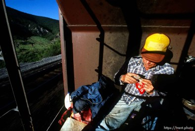 Casey rolls a cigarette while riding a train to Helper.