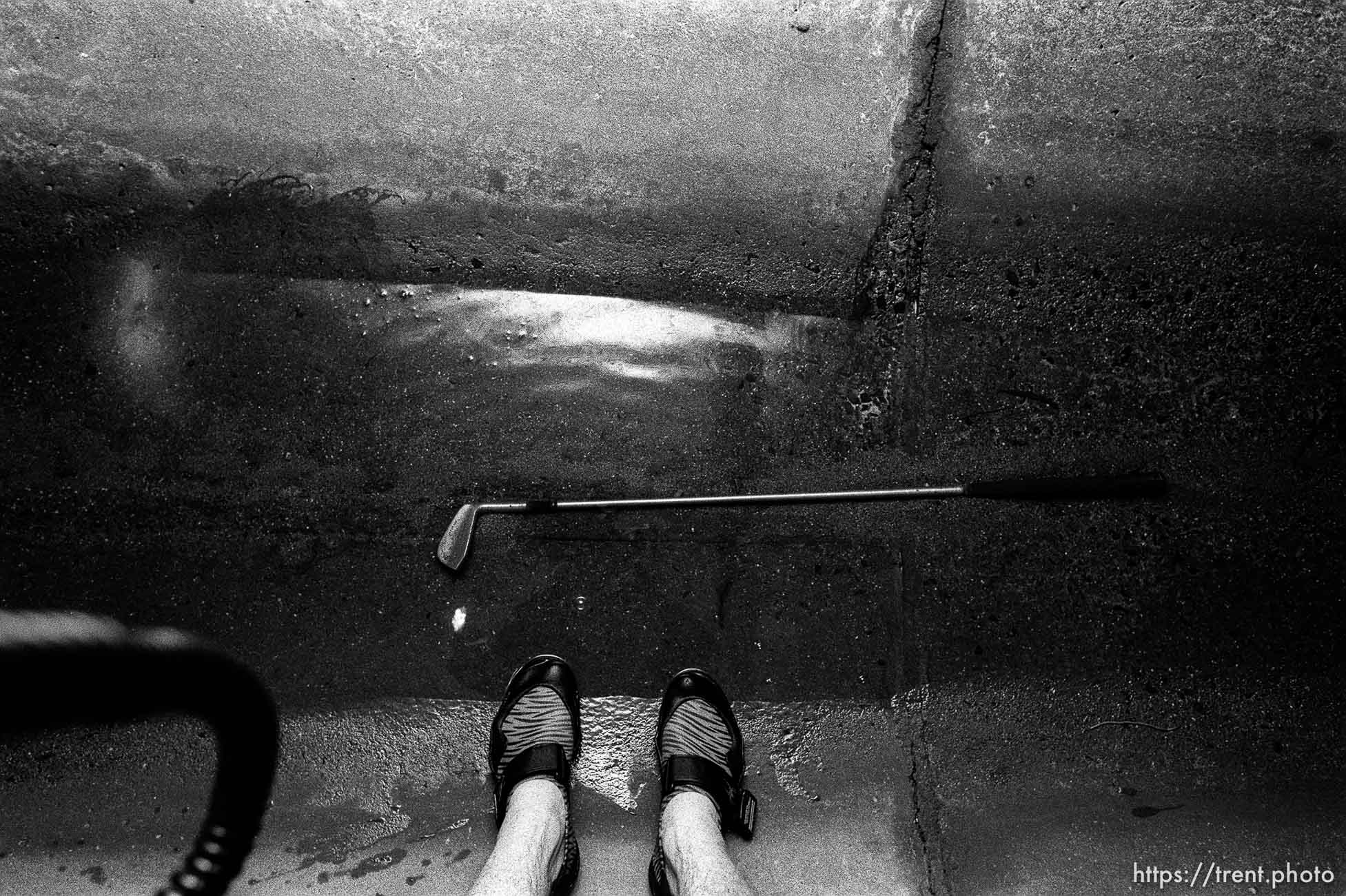 Trent feet and golf club in sewer pipe.