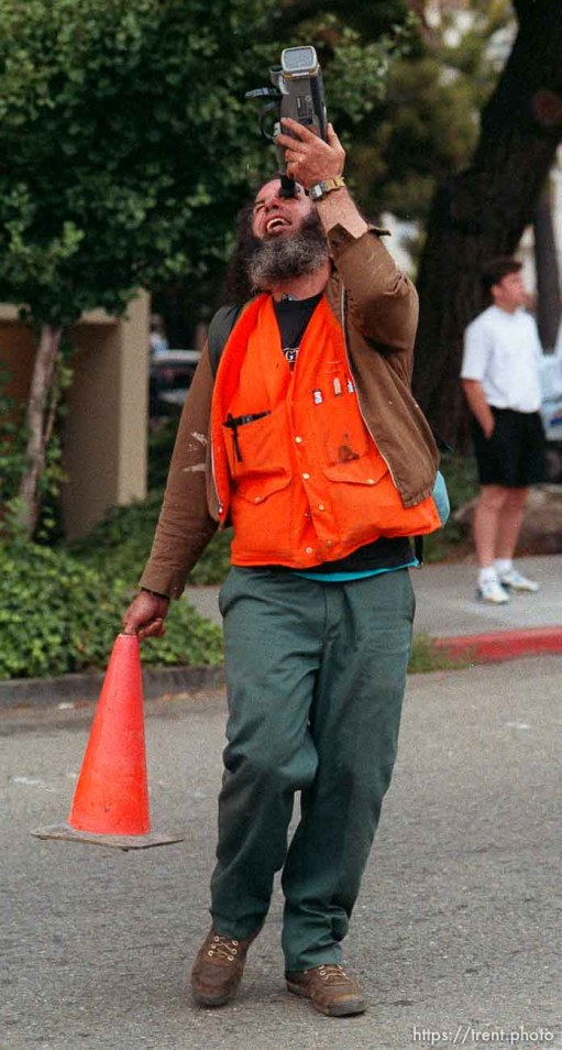 Strange protester with traffic cone and camcorder during riots and protests.