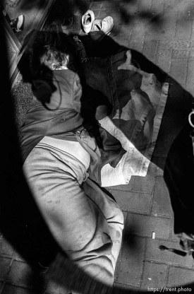 homeless woman sleeping on ground.