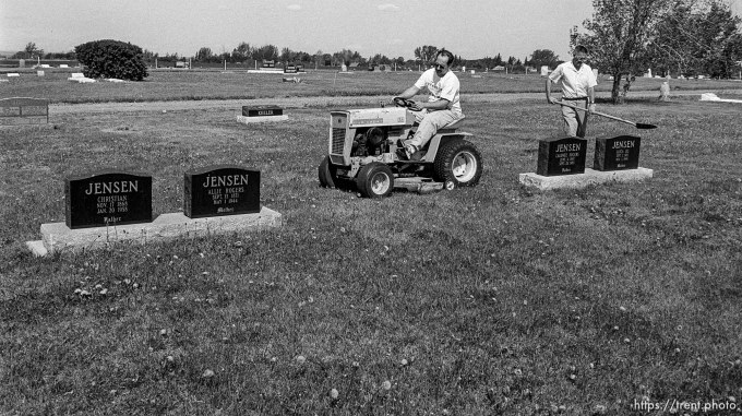 Scott Robinson and Ross Robinson mowing grass at cemetery