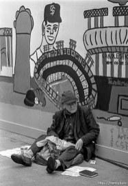 Homeless man under mural
