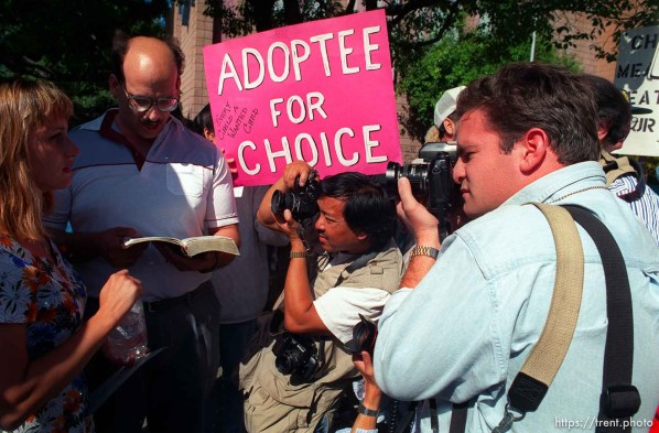 "Dan Honda and Dave Lowe shooting with ""adoptee for choice"" sign in background at Operation Rescue abortion protest at Planned Parenthood clinic."
