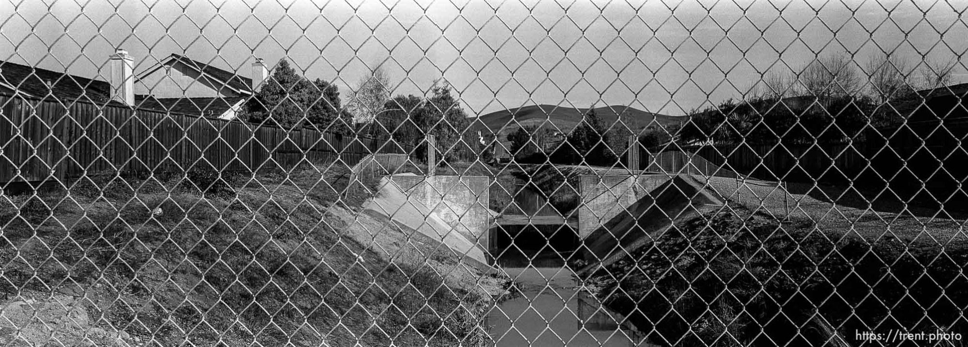View of San Ramon Creek. through chain-link fence