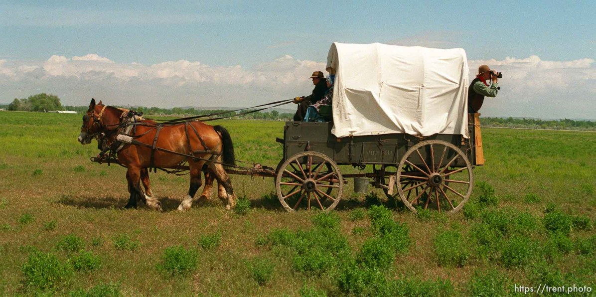 Lee Johnson, Spanish Fork, Utah, leans out the back of a wagon with a camcorder as the Mormon Trail Wagon Train stops for lunch.