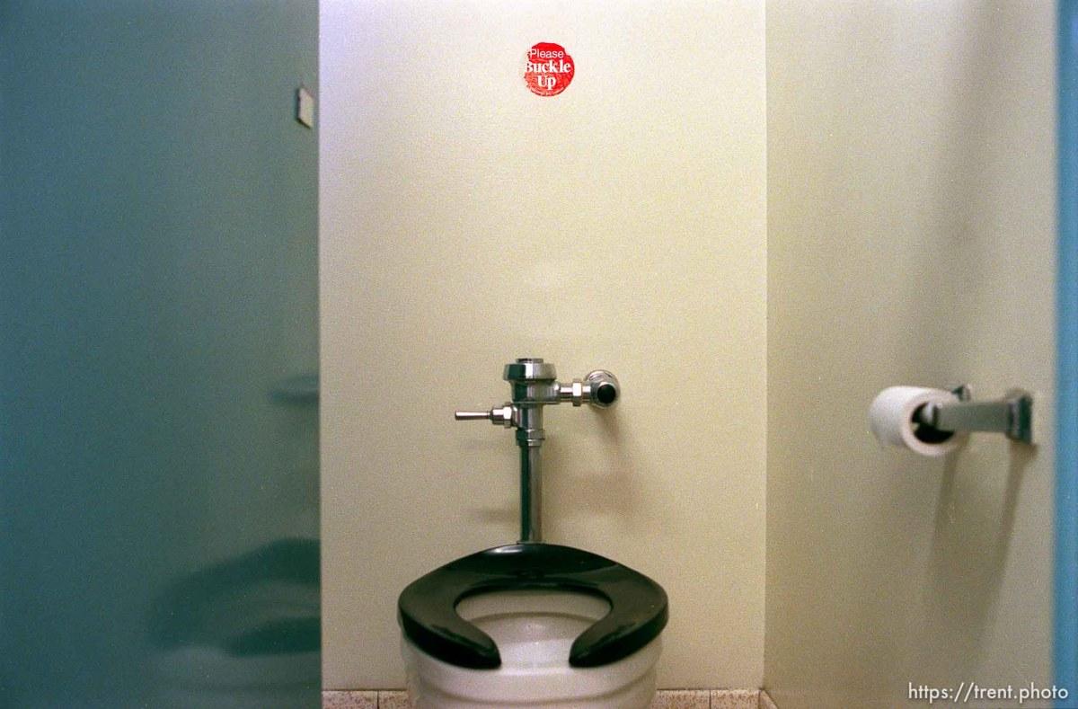 """Toilet with """"Please Buckle Up"""" sticker at Hill Air Force Base."""