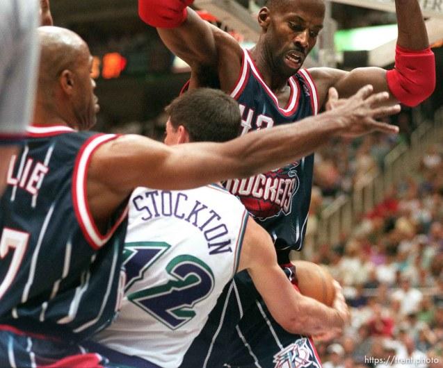 Utah's John Stockton passes around Houston's Kevin Willis (right), Mario Elie at left, at Utah Jazz vs. Houston Rockets, game 5 of the 1st round, NBA Playoffs. Jazz won.