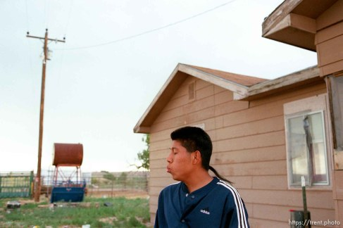 "Thomas Jenks whistles for his dog ""Champion"" outside of his home on the Ute Reservation."