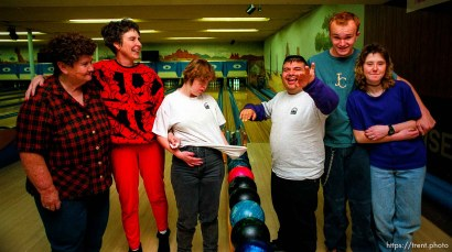 Disabled kids bowling and playing videogames. Group shot