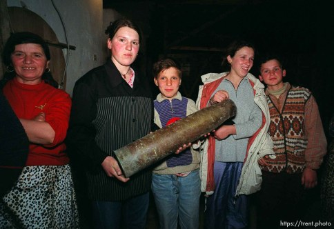 Kids holding an artillery shell casing at traditional dinner with the Hoxha family.