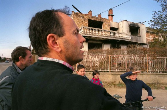 Shkelzen Binxhia talks about his brother's house (in background) which was an OSCE base during the KVM and later burned by Serbs.