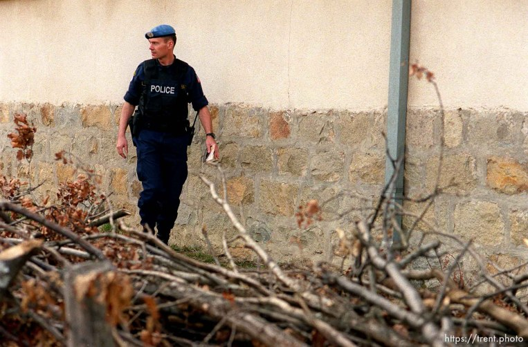 UNMIK police officer Zane Smith walking through a hillside village in Northern Kosovo