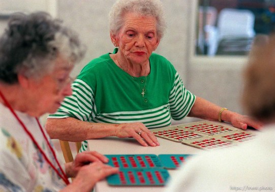 Jo Scorzato (green) checks her neighbor's cards playing Bingo in Kearns.