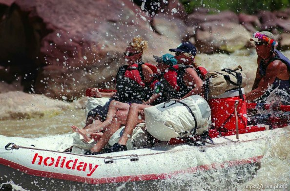 Nick Berich (right) pilots his boat through Hells Half Mile on a Native American river trip through Lodore Canyon and Dinosaur National Monument. Passengers, left to right, are Haley George, Hunter George, and their grandmother, Jan George.