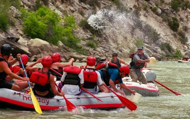 A waterfight breaks out as Bob Ligon throws a pail of water at the crew of a paddle boat on a Native American river trip through Lodore Canyon and Dinosaur National Monument.