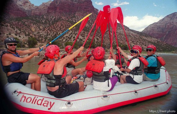 Crew of paddle boat holds oars aloft on a Native American river trip through Lodore Canyon and Dinosaur National Monument.