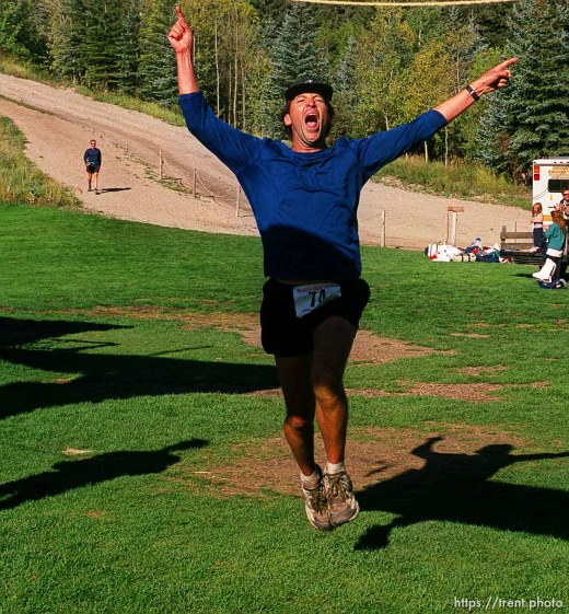 Ted Russell leaps for joy crossing the finish line at the end of the race, Sundance Ski Resort. Wasatch 100 Endurance Run.