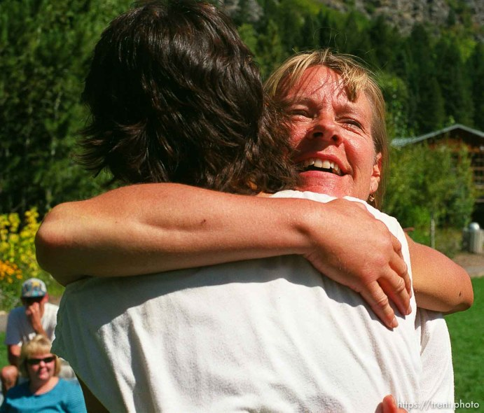 Lynn Yarnall (facing camera) embraces fellow runner Janine Duplessis at the end of the race, Sundance Ski Resort. Wasatch 100 Endurance Run.