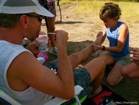 Tom Remkes eats yogurt while his wife Jamie rubs his feet near the Lambs Canyon aid station. Wasatch 100 Endurance Run.