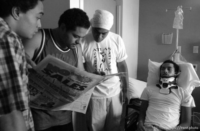 """""""East beat Highland!"""" During a hospital visit, friends and teammates Steven Vaenuku (left), Siale Vainuku (center) and Siaosi Vainuku (right) read the previous night's football scores to Una Taufa. West High football player Una Taufa suffered a severe neck injury in a game two weeks ago and is partially paralyzed. He has begun the long and arduous rehabilitation process at LDS Hospital. . 09/27/2001, 11:56:40 AM"""
