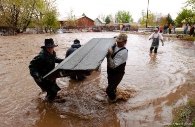 Volunteers work to save the Brigham City home of Linda and Arlin Kay as rain and melting snowpack raise the levels of Box Elder Creek and the Logan River. flood