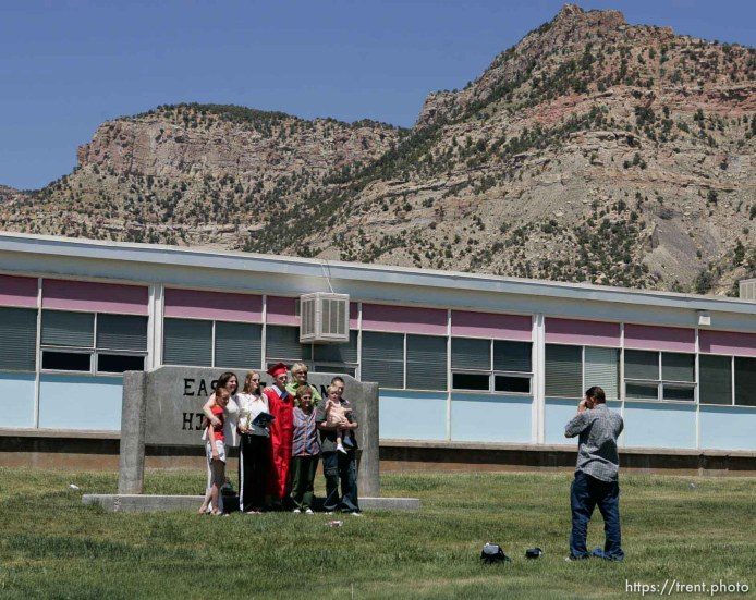 ECHS graduate Justin Ward has his photo taken with family members in front of the school and the Book Cliffs.