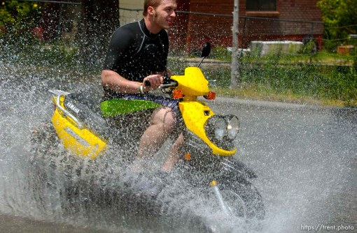A man in a wetsuit riding a scooter through water several inches deep along 700 South in Tooele Tuesday. Water from Settlement Canyon Reservoir turned the street into a shallow river after the area had 3.7 inches of rain Monday. Photo by Trent Nelson; 5.31.2005