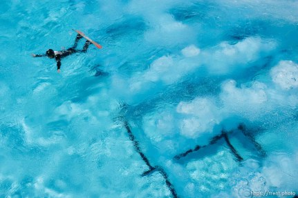 Park City - Graham Watanabe took advantage of a sunny day to practice aerials, snowboarding off the aerials jump and landing in the pool at the Utah Olympic Park. The air bubbles coming up from the bottom of the pool help soften the athlete's landing.