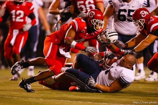 Salt Lake City - Utah vs. BYU college football Saturday, November 22, 2008 at Rice-Eccles Stadium. BYU RB Fui Vakapuna (1) tackled by Utah defensive back Terrell Cole (21), loses his helmet. Utah running back Matt Asiata (4)