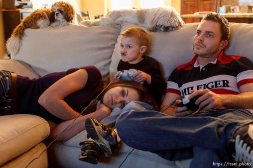 "Trent Nelson | The Salt Lake Tribune Jen Carver rests while her son T.J. and fiancé Daniel Comer play videogames Thursday, March 29, 2012 in Ogden, Utah. The family dogs Charlie Dragon Superhero, left, and Tyke, are on top of the couch. U.S. Army veteran Jen Carver served two tours in Iraq and is now a full time college student with an on-campus job while raising her 4-year-old son. After a long day of school and work, Carver keeps her evenings as, ""strictly time for my boy."""