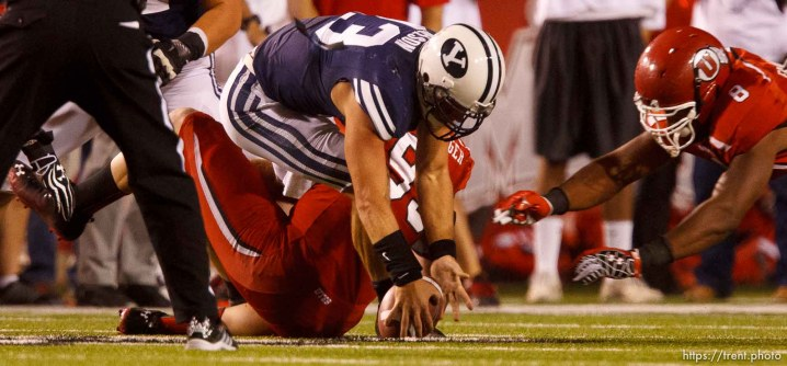 Trent Nelson | The Salt Lake Tribune Brigham Young quarterback Riley Nelson (13) recovers his fumble as he's sacked by Utah defensive end Joe Kruger (99) as Utah hosts BYU college football in Salt Lake City, Utah, Saturday, September 15, 2012. Utah defensive end Nate Fakahafua (8) at right.