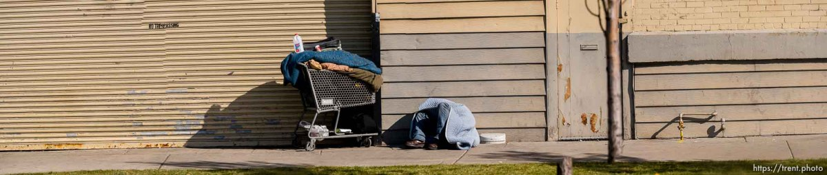man sleeping on sidewalk with grocery cart, Salt Lake City, Friday March 28, 2014.