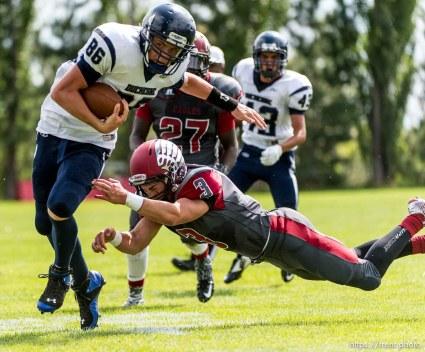 Trent Nelson | The Salt Lake Tribune Duchesne's Wyatt Remund dodges Layton Christian's Bailey Kenter en route to scoring the first touchdown of the Utah high school football season, in Layton Thursday August 21, 2014.