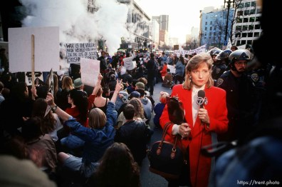 Television reporter in the middle of sit-down protest on Market Street at Gulf War protest.