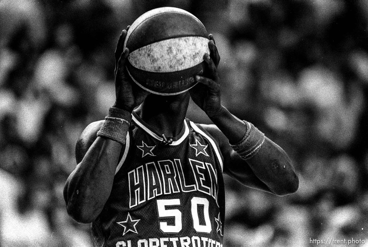 Harlem Globetrotter with ball over his head.