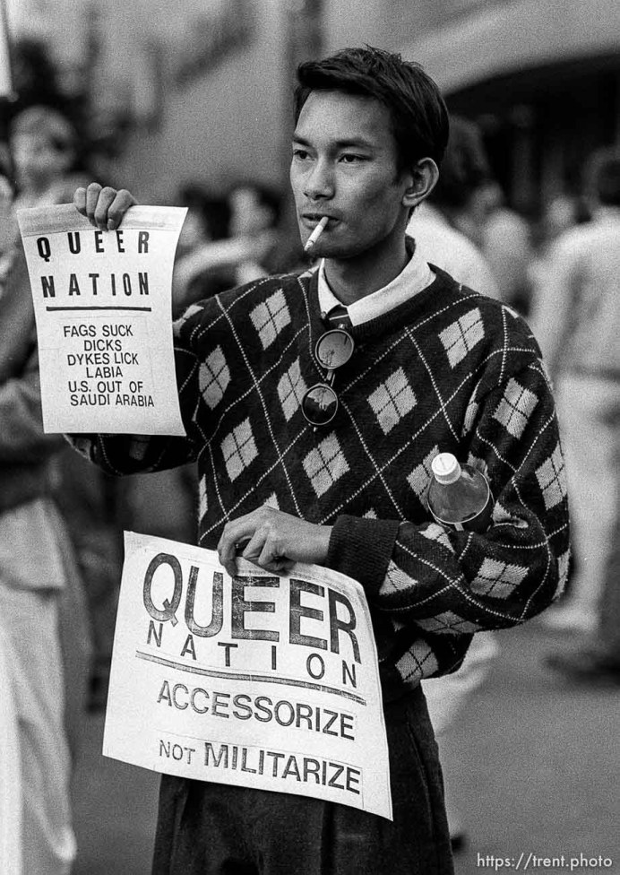 Man holding Queer Nation flier at Gulf War protest.