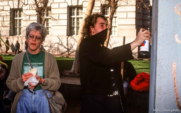 "A member of the self-named ""Punx for Peace"" spray paints a monument while a woman gives the stink-eye during an Anti-war Gulf War protest."