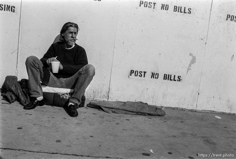 """Homeless man and white wall with """"post no bills"""""""