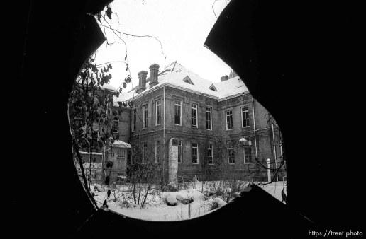 the old Academy Building seen through a broken window.