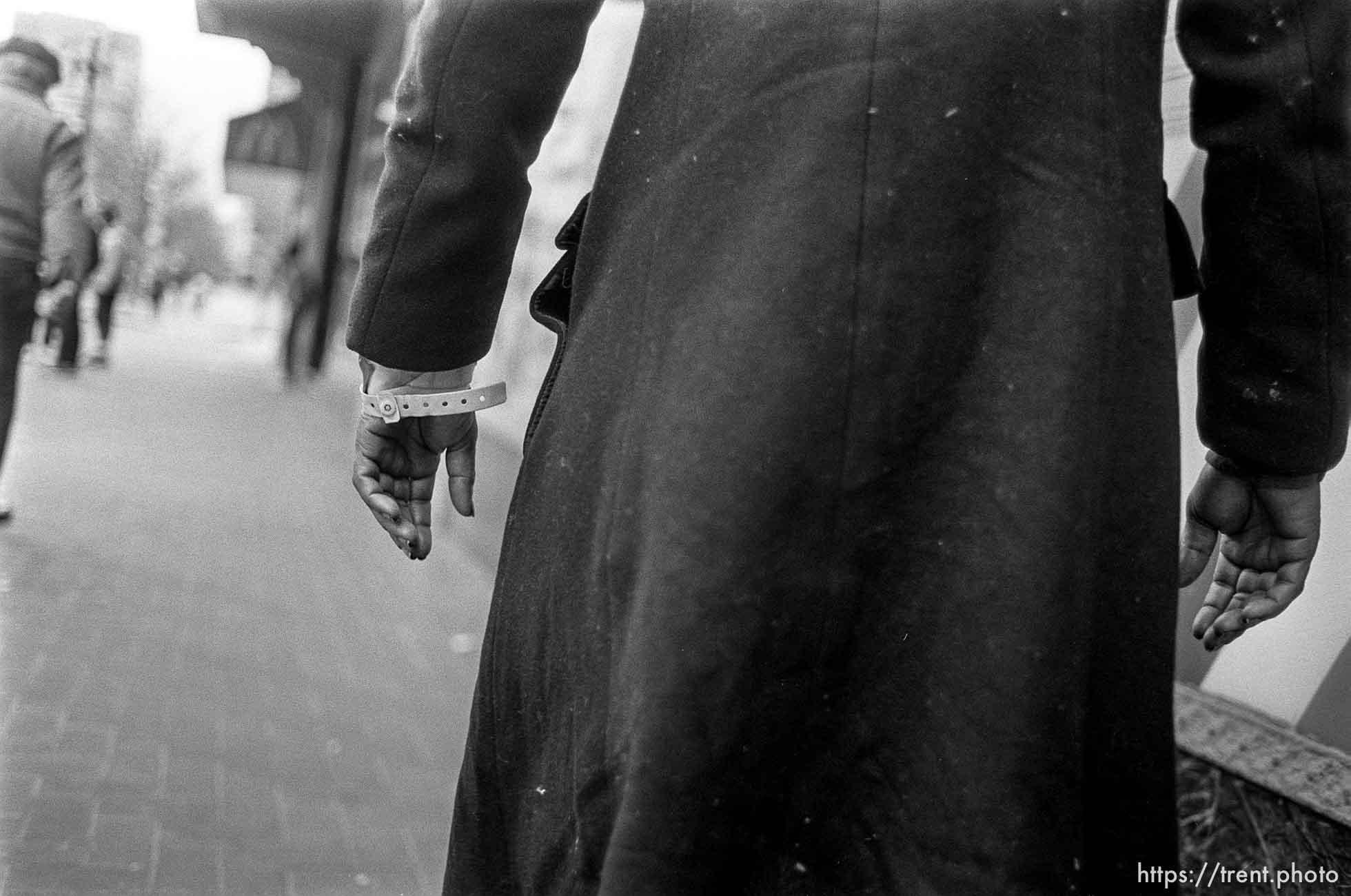 Man with hospital bracelet and long, dark coat
