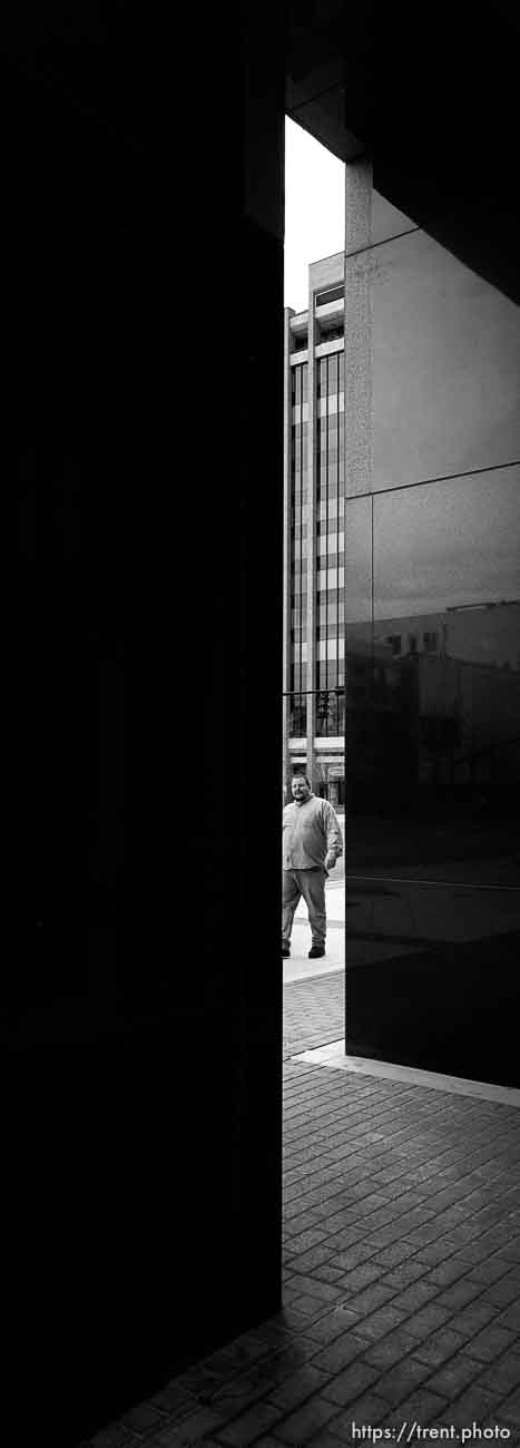 Man walking downtown, seen through walls of American Stores Building.