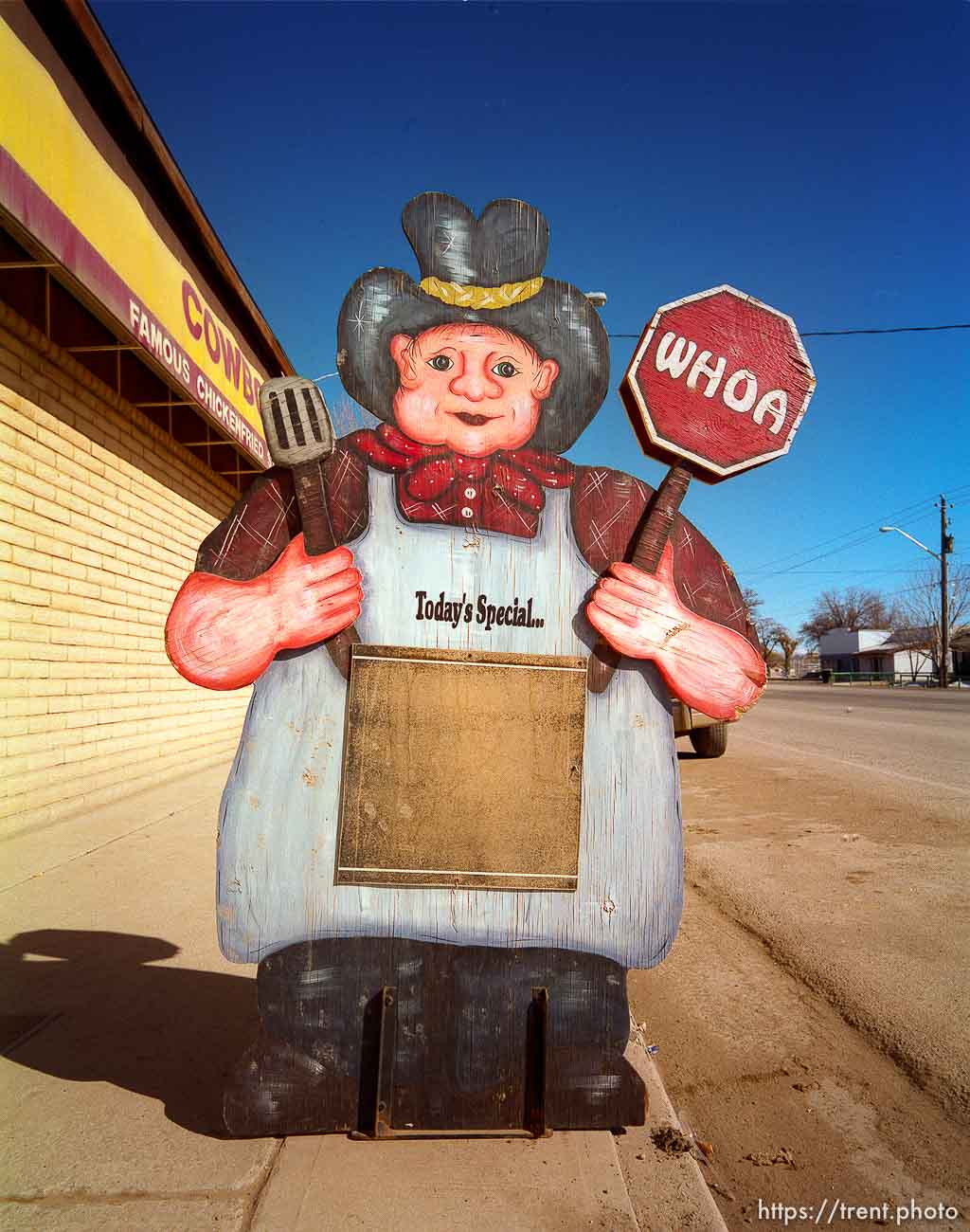 Cowboy cutout in front of roadside cafe.