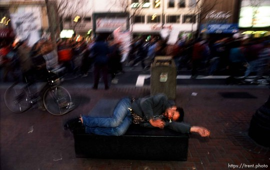 Homeless man on a bench as parade of protesters passes him on Market Street during Anti-war Gulf War protests.