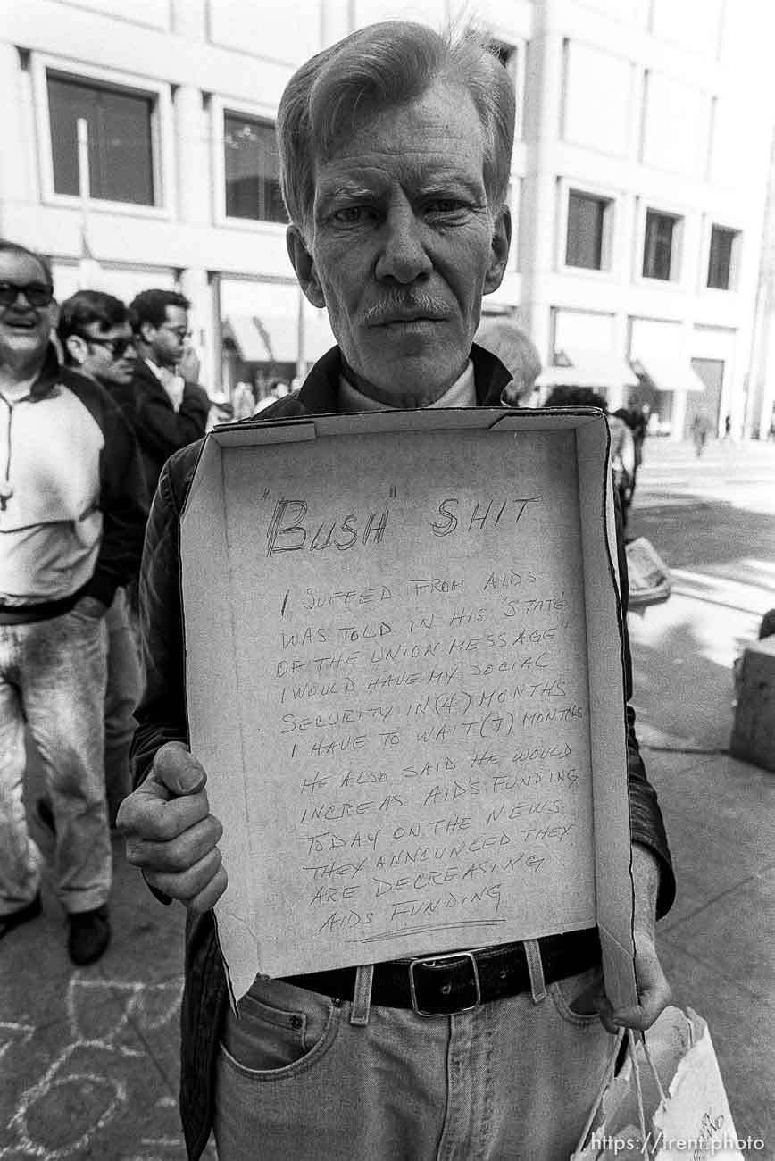 """Man with protest message written on box """"Bush Shit"""" at Act-Up protest during visit of President Bush"""