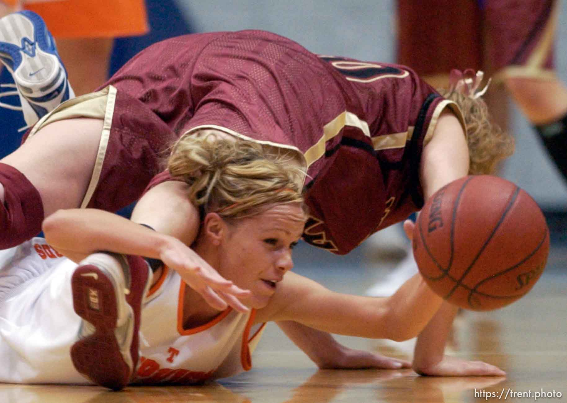 Timpview's Jessica Harmon shows the determination that brought her team to the state championship game as she dives for a loose ball underneath Mountain View's Mallary Gillespie. Utah's 4A state championship girls basketball game.