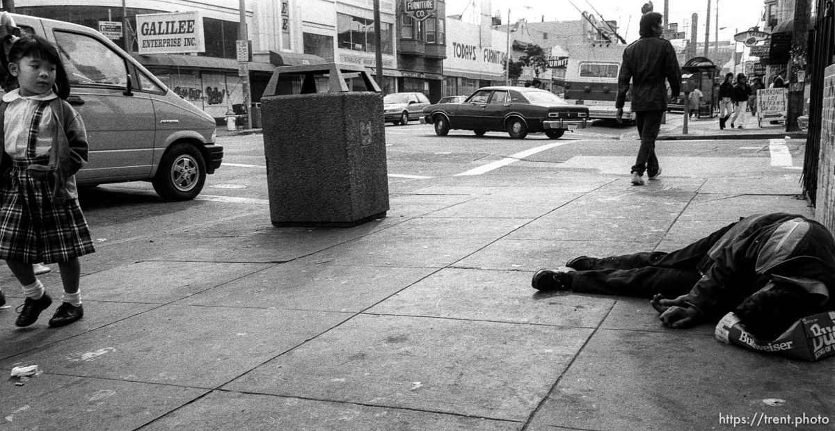 Young girl stares at man sleeping on the street in the Mission District