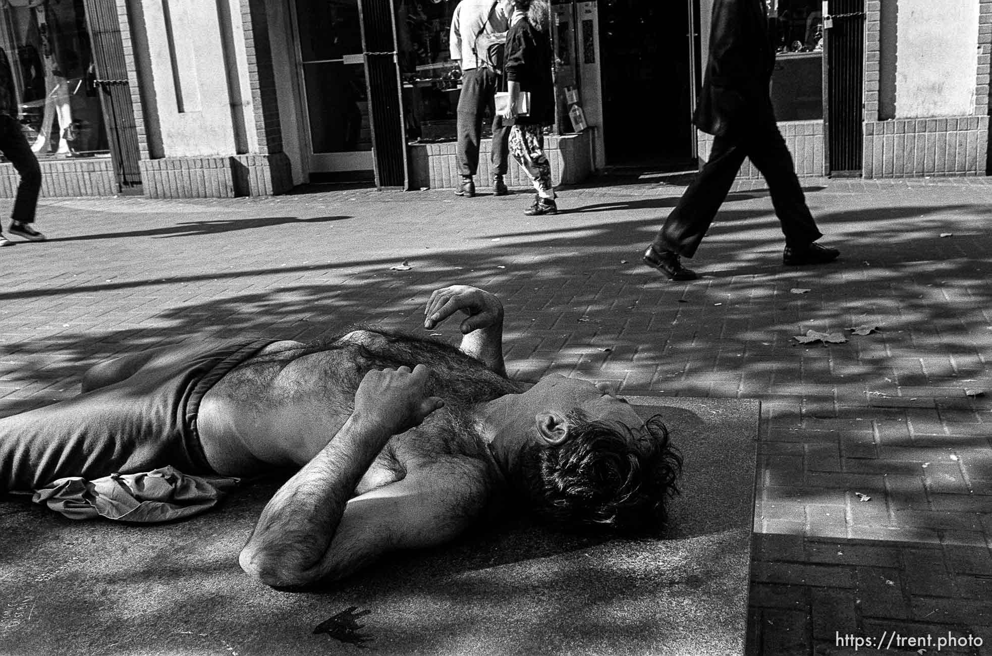 Shirtless man sleeping on street. Leica hip shots on the street.